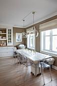 Langer Esstisch und transparente Stühle in der Küche mit beigefarbenen Wänden