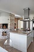 Abzugshaube über Kochinsel und gemauerter Kamin in offener Küche