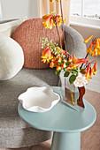 Blumen auf hellblauem Beistelltisch mit gewellter Vase