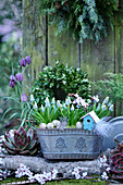 Jardiniere with grape hyacinths, Easter eggs, feathers and decorative birdhouses