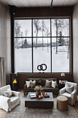 Cosy living room in natural colours with view of snowy landscape