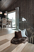 Cushion and animal fur on stairs with seat in the wooden house
