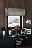 Lanterns, bouquet of flowers and photos on black lowboard in front of window