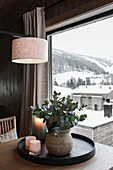 Vase with eucalyptus branches and lanterns on dining table, view of snowy landscape