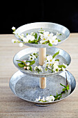 Flowers in homemade etagere made of zinc plates and wooden stick