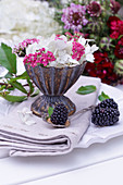 Hydrangea blossom and red yarrow in a silver sundae