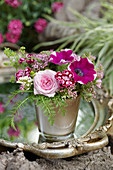 A small bouquet of rose blossoms, petunias, carnations, yarrow and sparrows
