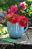 Red verbena flowers in a blue mug