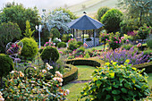 Sloping garden with pavilion and bed with rose stems, bordered with box hedge
