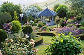 Hanggarten mit Pavillon und Beet mit Rosenstämmchen, eingefasst mit Buchshecke