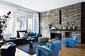 Light blue designer armchairs and sofa in the living room with natural stone wall