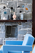 Light blue designer armchair in front of stone wall in living room