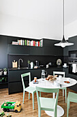 Black fitted kitchen, white table and green chairs, toys on the floor