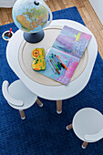 Colouring book with pencils and globe lamp on children's table