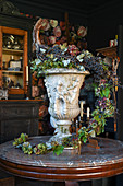 Ambitious, autumnal flower arrangement with grapes in urn