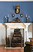 Stack of antique leather suitcases in disused fireplace in blue and white wall