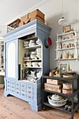 Geschirr im offenen blauen Schrank und nostalgische Deko