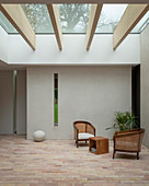 Minimalist seating area with brick floor below glass ceiling