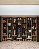 Vases, jugs and sculptures on modern shelves against dark wall