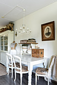 Old chairs at white wooden table in shabby-chic dining room