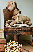 Antique soft toy on old chair and bouquet of dried roses