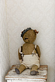 Vintage-style arrangement of old, threadbare teddy bear wearing a crown