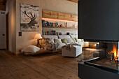 Polstersofa, darüber Holzregale in gemütlichem Wohnzimmer, Kaminofen im Vordergrund