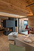 Blick auf Kamin in offenem Wohnraum mit Dielenboden und Holzdecke