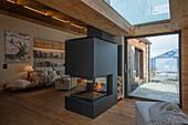 Kaminofen neben Terrassentür in offenem Wohnraum mit Dielenboden