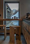 Frühstückstheke und Barhocker aus Massivholz vor Panoramafenster