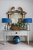 Zwei Tischleuchten und Pflanzenkorb auf Konsole, dahinter antiker Spiegel