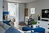 Blick über Sofa auf blaue Ottomane als Couchtisch und weiße Kommode