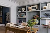 Grauer Regalschrank und Holz-Schreibtisch im Arbeitszimmer
