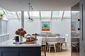 Kücheninsel und Essbereich unter Glasdach