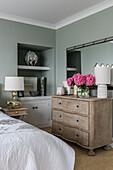 Holzkommode und eingebautes Regal im Schlafzimmer mit grauen Wänden