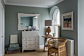Weißer Sekretär, Wandspiegel, Beistelltisch und Rattansessel im Vorzimmer