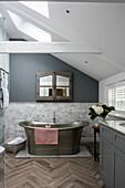 Freistehende Badewanne aus Kupfer im Badezimmer mit Dachschräge