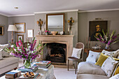 Fresh flowers in living room with limestone fireplace