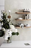 Holzregale mit Geschirr an der Wand, Strauß aus weißen Blumen auf Tisch
