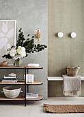 Eisenkonsole mit ovalen Holzregalen, darauf Bücher, Dekoration und Blumenstrauß