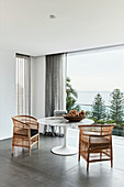 Two wicker armchairs at designer table in front of balcony with panoramic view