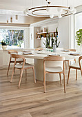 Großer runder Tisch mit hellen Holzstühlen im modernen Esszimmer