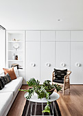 White fitted cupboards and wooden floor in living room
