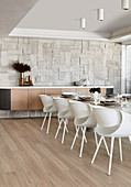 Modern chairs at long dining table in luxurious dining room decorated in beige
