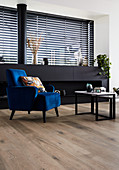 Blue velvet armchair in front of black sideboard in living room