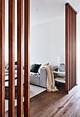 Blick durch Raumteilerwände aus Holz ins Wohnzimmer