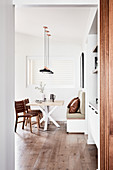 View into modern dining room in natural shades with wooden floor