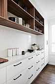 Narrow kitchen counter with white base units below open-fronted shelves