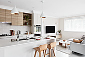 Modern interior decorated in white and beige with open-plan kitchen area