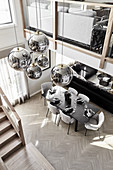 Luxurious, open-plan interior with gallery level and spherical lampshades